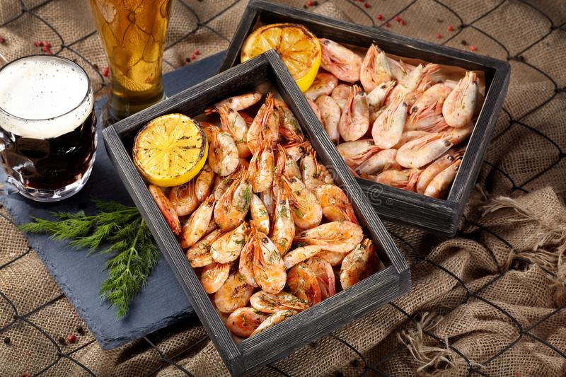 Two wooden trays with boiled and fried shrimp. Two wooden trays with boiled and fried shrimp next to a glass of dark and light beer stock photography