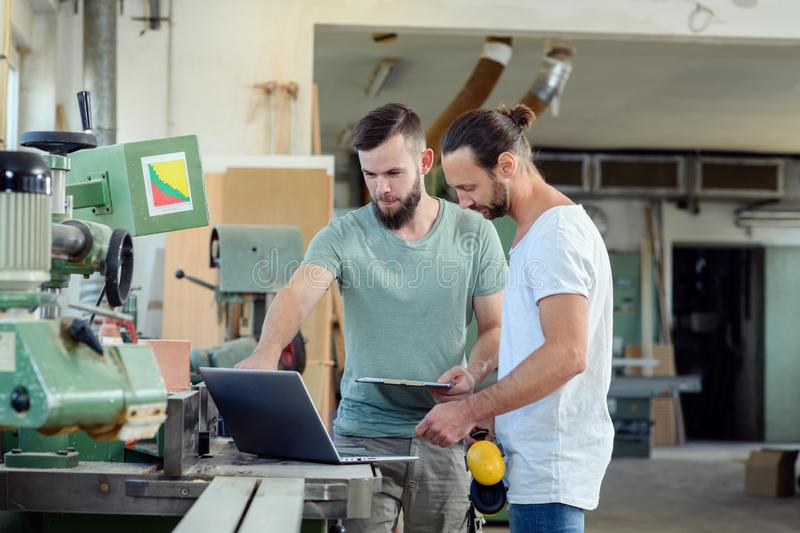 Two worker in a carpenter`s workshop with computer and clipboard. Two worker in a carpenter`s workshop with clipboard and computer royalty free stock photos