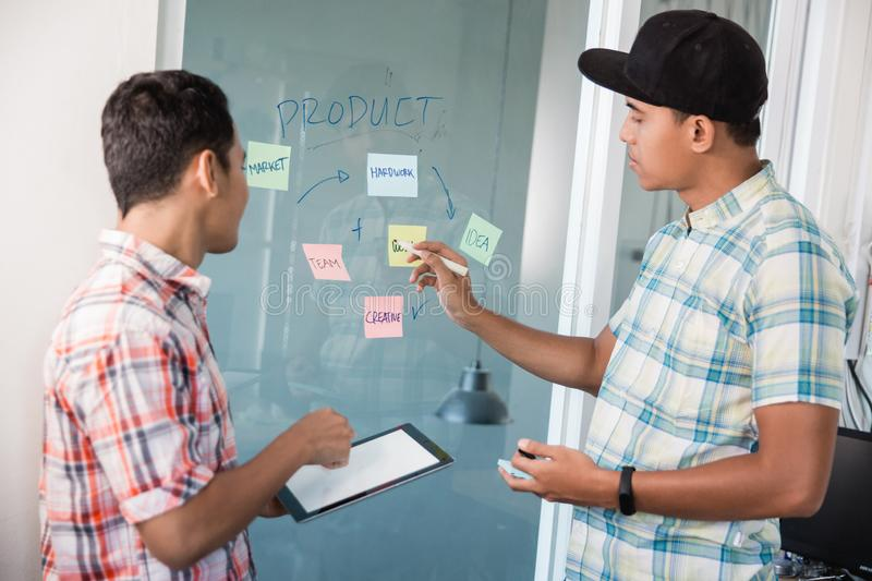 Two worker correcting a word on paper notes to make material discuss on meeting. Today royalty free stock photos
