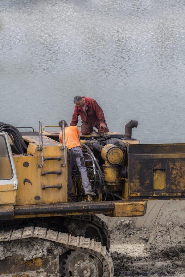 Two worker repairing engine of excavator stock image