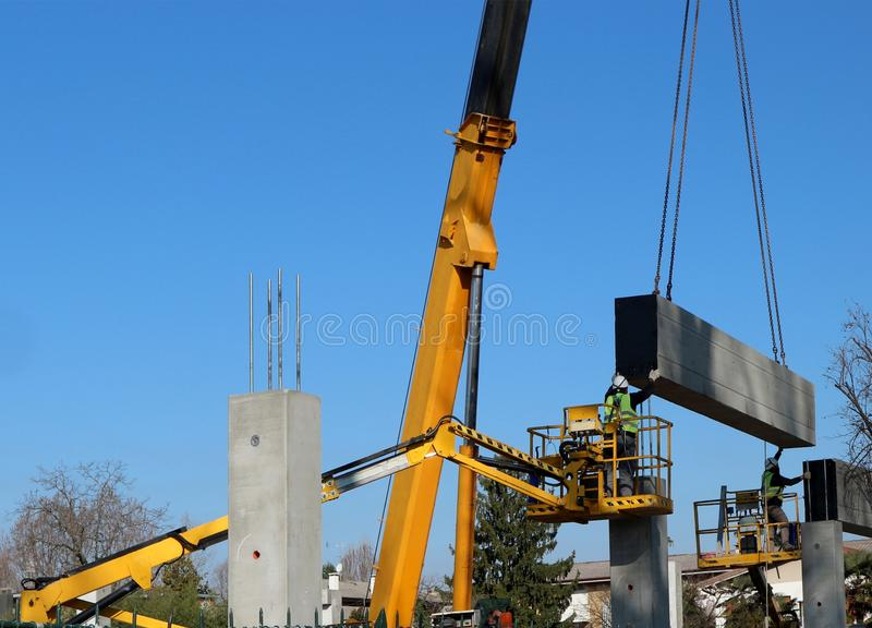 Two workers on two cherry pickers install a prefab concrete slab, lifted by a telescopic crane, on the new wall of the building u royalty free stock photo
