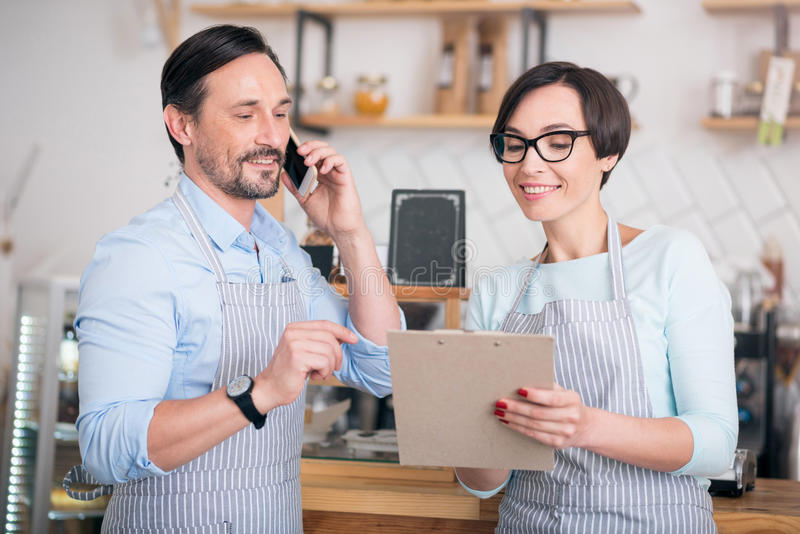 Two workers communicating in cafe. Being friendly. Positive and merry cafe workers holding folder and using smart phone royalty free stock image