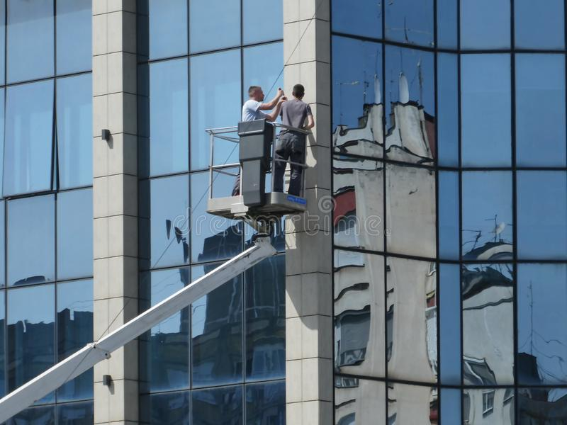 Two workers on the crane with hydraulic aerial platform fixing problem on glass building stock photo