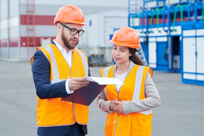 Two Workers Discussing Project Outdoors. Waist up portrait of two modern factory workers wearing hardhats discussing production over clipboard outdoors, copy royalty free stock images