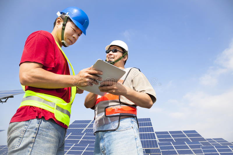 Two workers discussing with tablet. Pc before solar power station stock photography