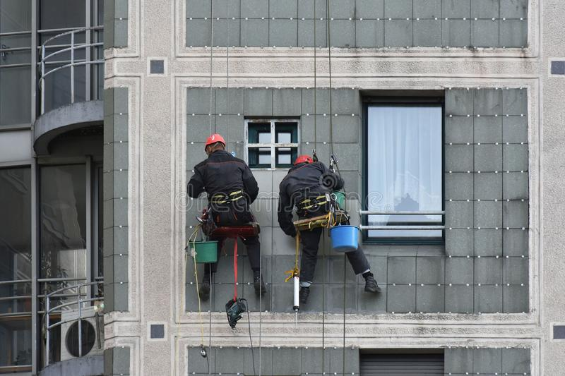 Two workers fix facade hanging. On the rope stock image