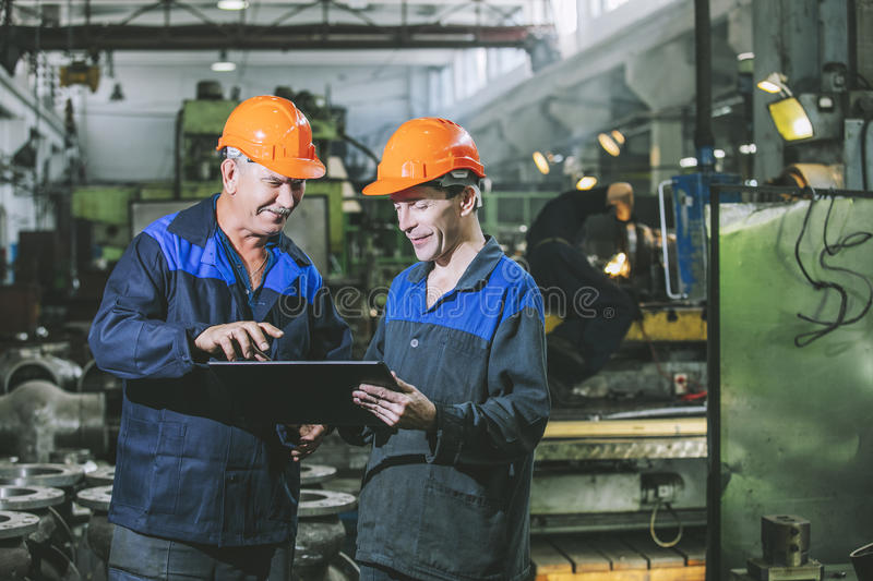 Two workers at an industrial plant with a tablet in hand, workin. G together manufacturing activities
