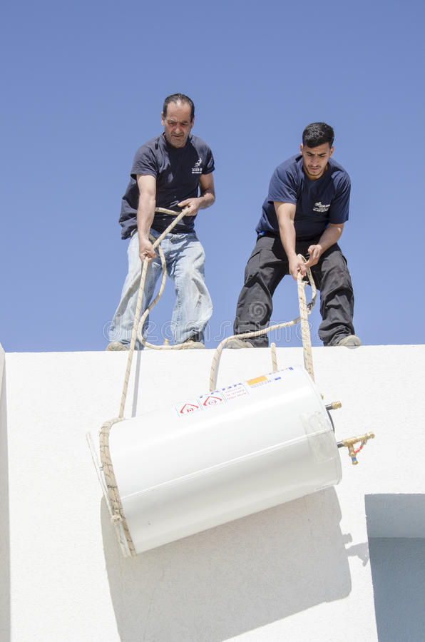 Two workers install solar boiler roof - Mitzpe Ramon, Israel. Middle East- Mitzpe Ramon, Israel. February 29,The installation of new solar water heaters stock photography
