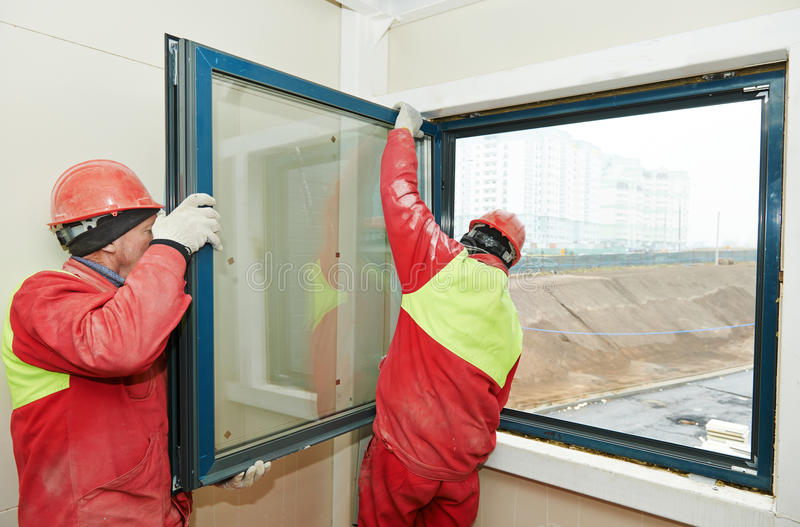 Two workers installing window royalty free stock image