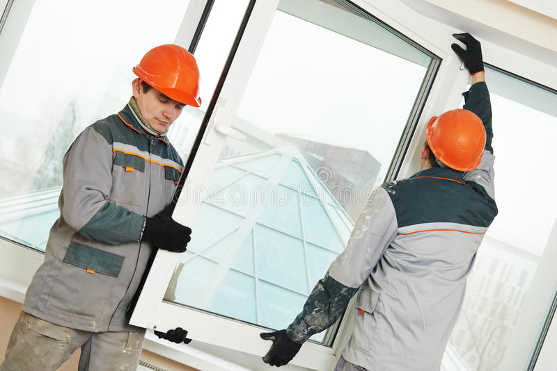 Two workers installing window stock photography
