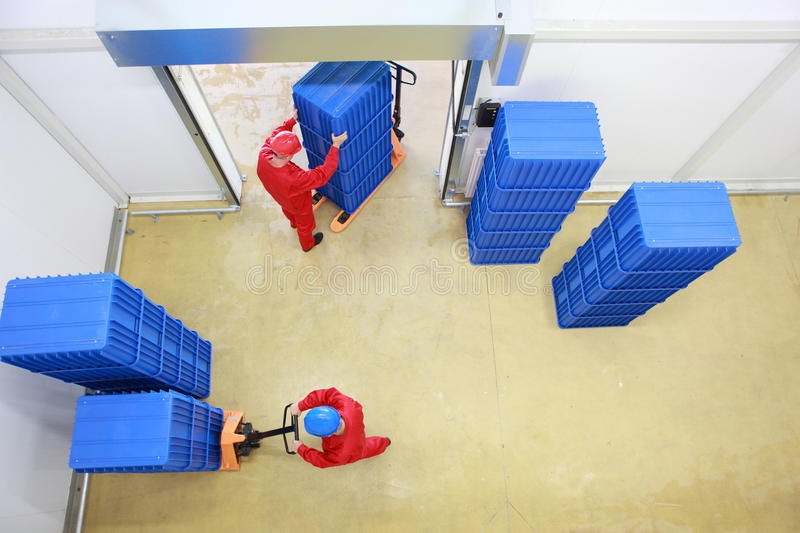 Two workers loading plastic boxes stock image