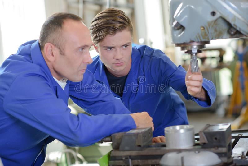 Two workers looking at drill bit on industrial machine. Drill royalty free stock photo