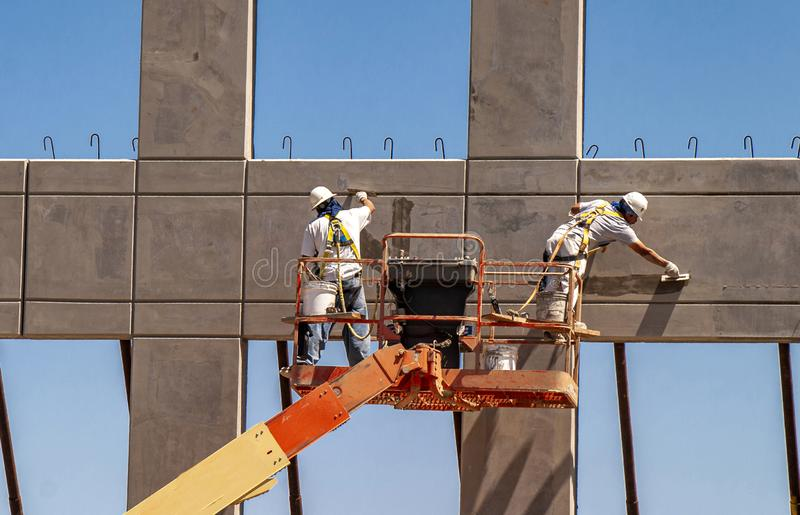 Two workers on man lift working on prefab wall using trowels royalty free stock photo