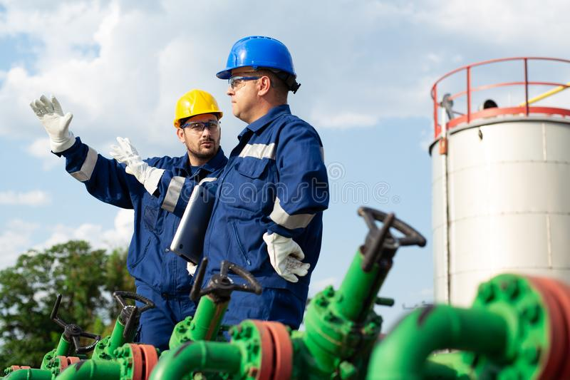 Two workers in the oilfield. Oil and gas concept. Young Engineer power and energy using laptop on location site royalty free stock photo
