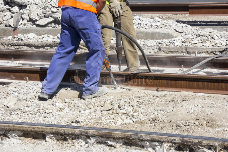 Two Workers with pneumatic hammer. Drill equipment breaking Concrete at construction site stock photos