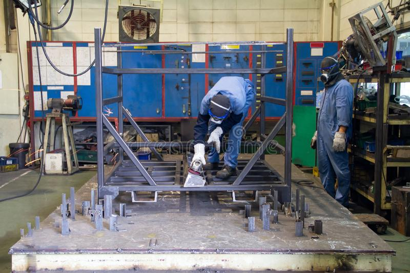 Two workers in production plant. Two workers welding in Steel factory Grinding steel On the steel floor royalty free stock photography