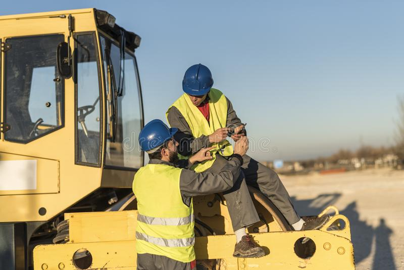 Two workers talking in work break on steamroller bulldozer vehicle stock photography