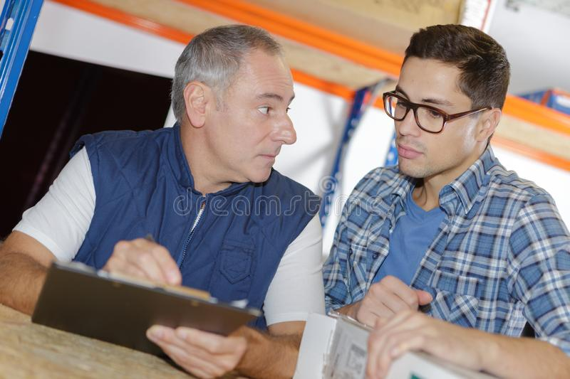 Two workers in warehouse. Two workers in a warehouse royalty free stock photo