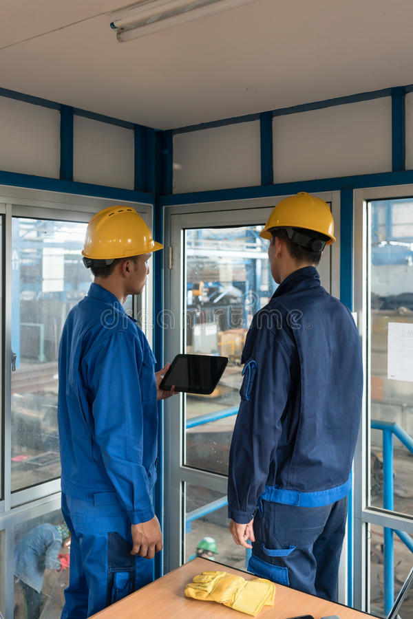 Two workers wearing hard hats while using a tablet PC royalty free stock photos