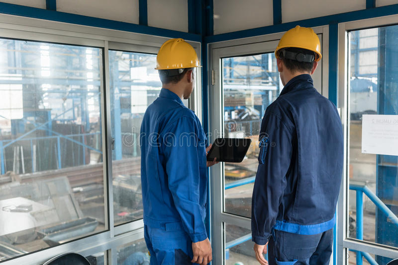 Two workers wearing hard hats while using a tablet PC stock photos