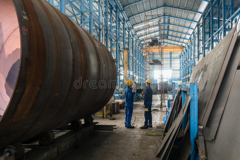 Two workers wearing yellow hard hat and blue uniform stock photography