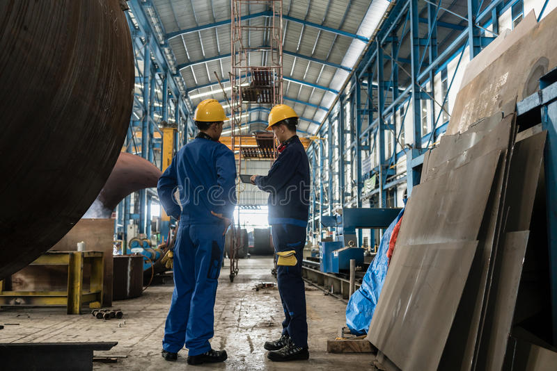 Two workers wearing yellow hard hat and blue uniform stock photo