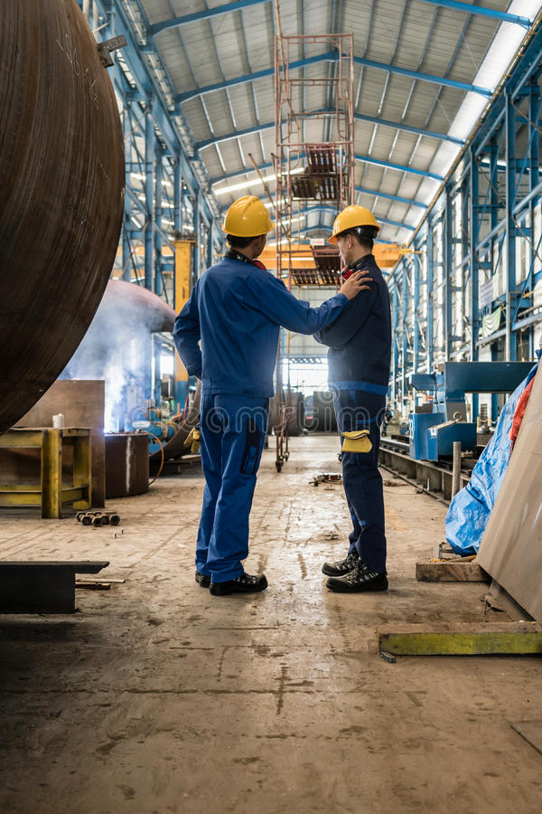 Two workers wearing yellow hard hat and blue uniform stock image