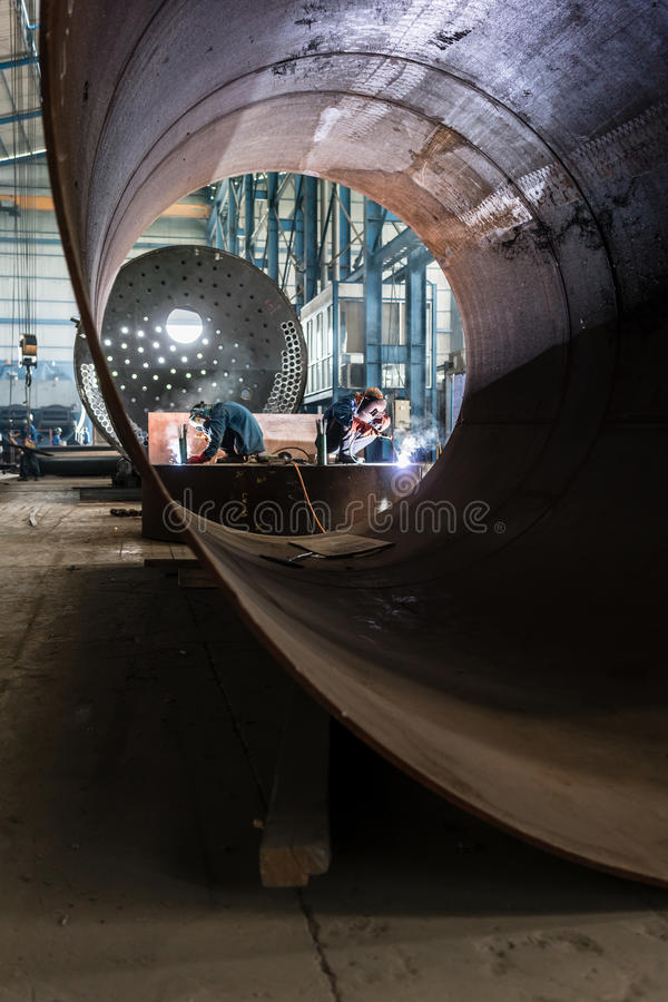 Two workers welding in a factory manufacturing boilers stock photography