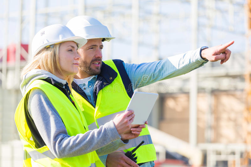 Two workers working outside with a tablet on a construction site stock photo