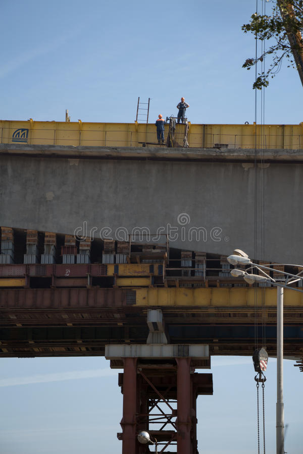Two workers in workwear high on a bridge processing construction stock photography