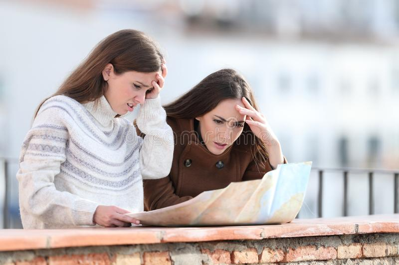 Worried lost tourists checking map on winter holidays royalty free stock photography