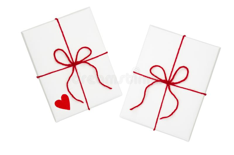 Two wrapped white gift box with red ribbon and bow isolated on white background, top view royalty free stock photography