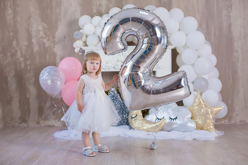 Beautiful baby girl in white pink dress posing in studio shoot with big huge silver baloon number 2 and plenty white airy baloons royalty free stock photos