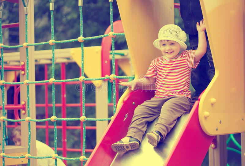 Two-year child on slide stock images