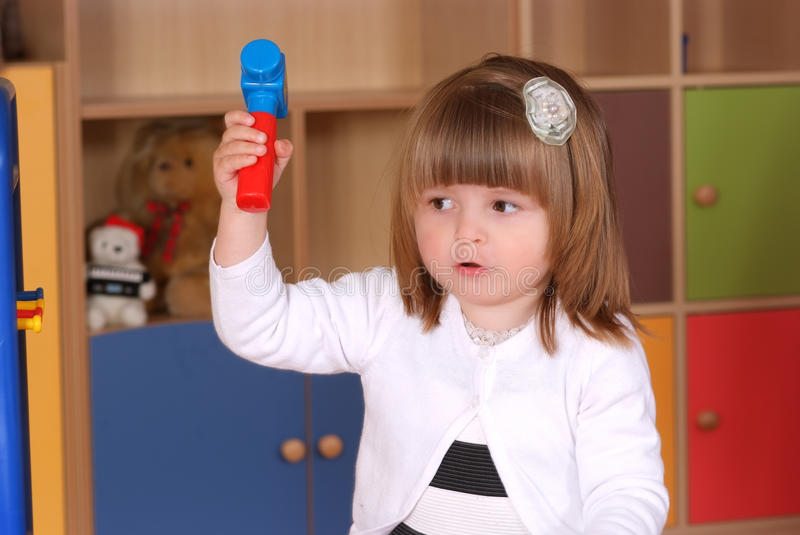 Two-year girl playing and learning in preschool. Child in the nursery is playing in building royalty free stock image