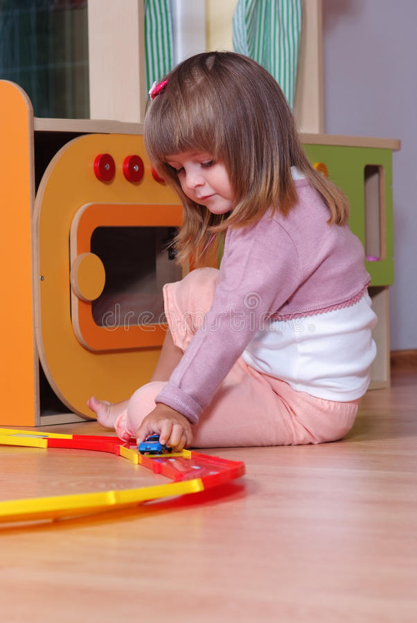 Two-year girl playing and learning in preschool. Child in a nursery playing with toy cars stock photo