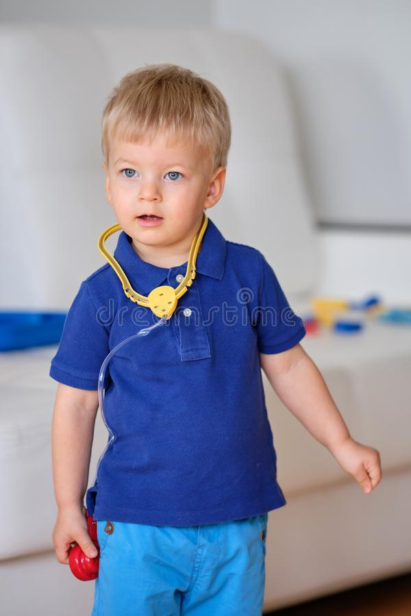 Two year old boy playing doctor stock photos