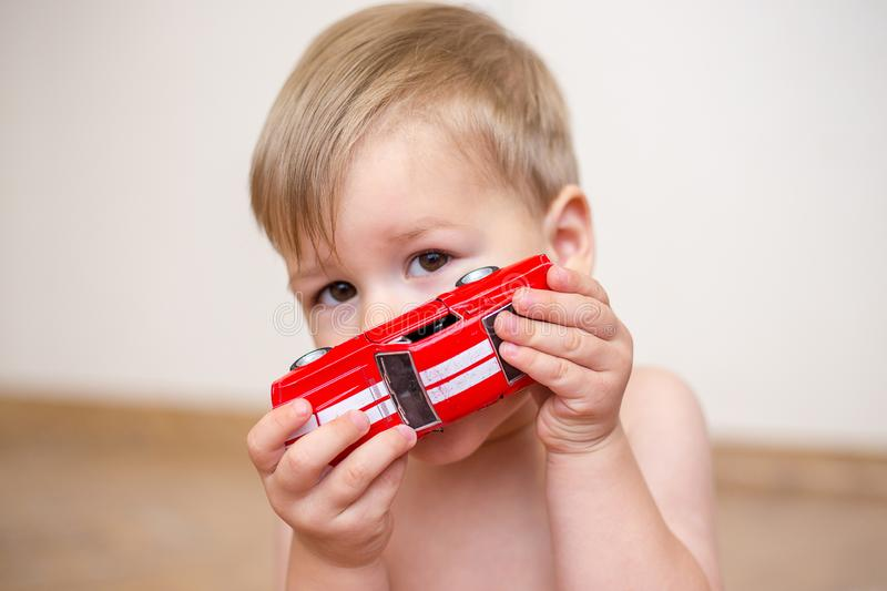 Two year old boy is playing with a red toy car royalty free stock photo