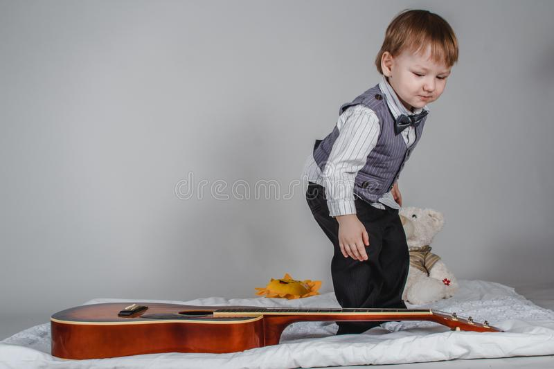 Two year old Caucasian boy in bow tie and vest with acoustic guitar on grey background stock photography