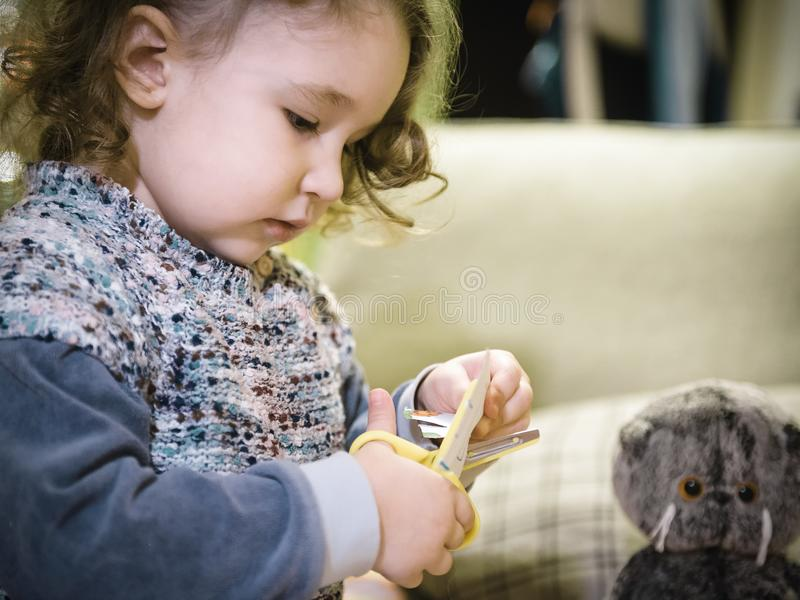 Two-year-old child cuts paper with scissors stock photography