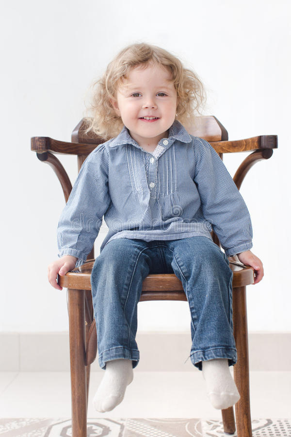 Two year old child sitting on chair full body royalty free stock images