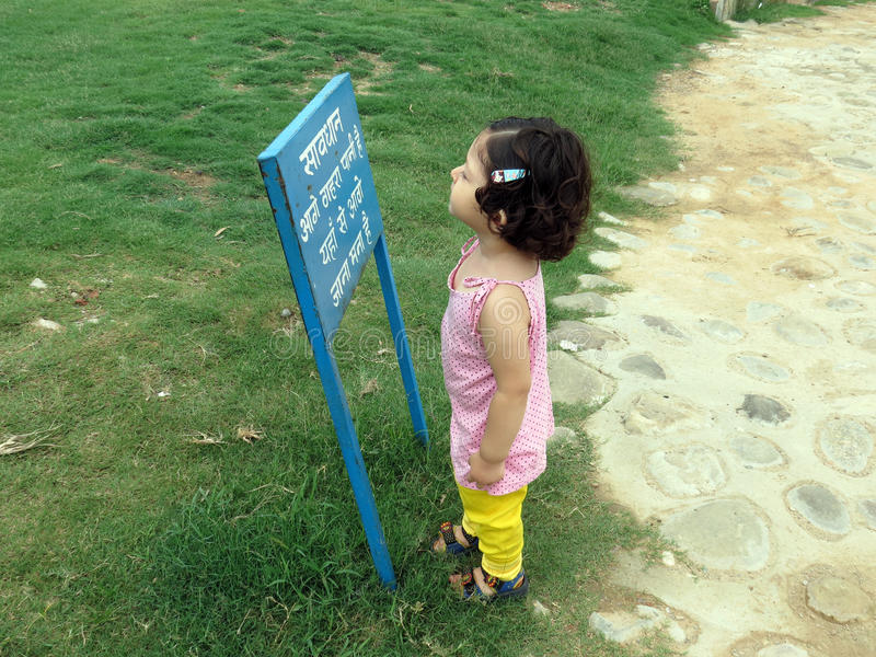 Two year old girl reading a sign board stock images