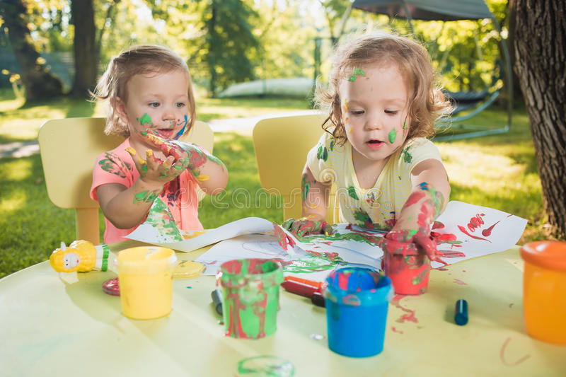Two-year old girls painting with poster paintings together against green lawn. Two-year old girls painting with poster paintings and sitting at a table together stock photo