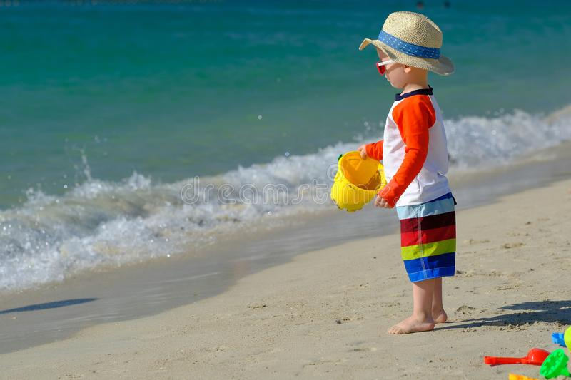 Two year old toddler playing on beach stock image