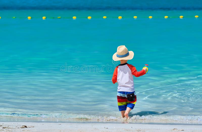 Two year old toddler playing on beach stock photography