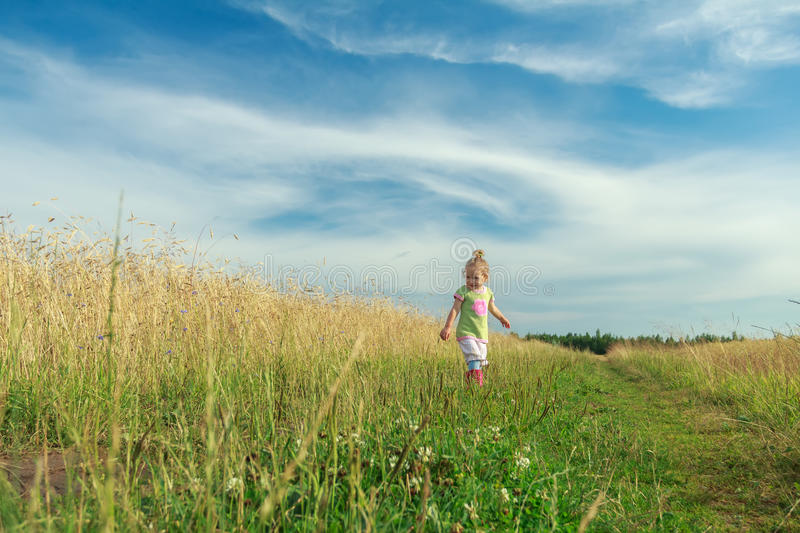 Two years old blonde toddler girl walking by foot on dirt road among cereal field. Two years old blonde toddler girl is walking by foot on dirt road among cereal stock images