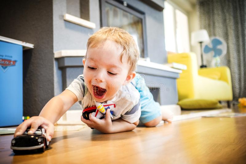 Two years old boy is playing with his toys indoors stock photography