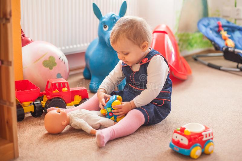 Little girl with doll. A two years old girl playing with doll on the floor in playground stock photos