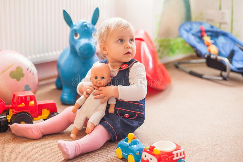 Little girl with doll. A two years old girl playing with doll on the floor in playground royalty free stock photos