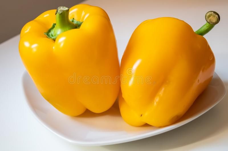 Two yellow bell peppers on the white porcelain dish closeup - Image. Big yellow bell peppers capsicum on the white porcelain dish closeup - Image stock image